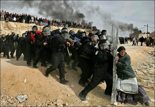 "1 Feb 2006 Amona Expulsion. We lost the battle for the 9 houses destroyed later in same day. But this one woman represents ""Am Israel Chai"". In the end we will claim victory over both Arabs and the insane leaders in the Knesset. It is unclear which poses a greater threat to the future survival of the modern State of Israel. -- Reporter Shlomo Wollins"